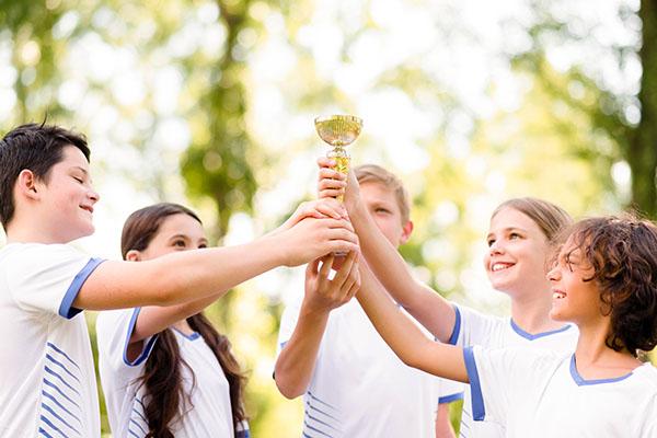sport excursions kids team raising trophy